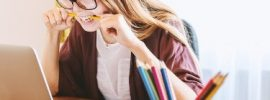 frustrated student with laptop and pencil in mouth
